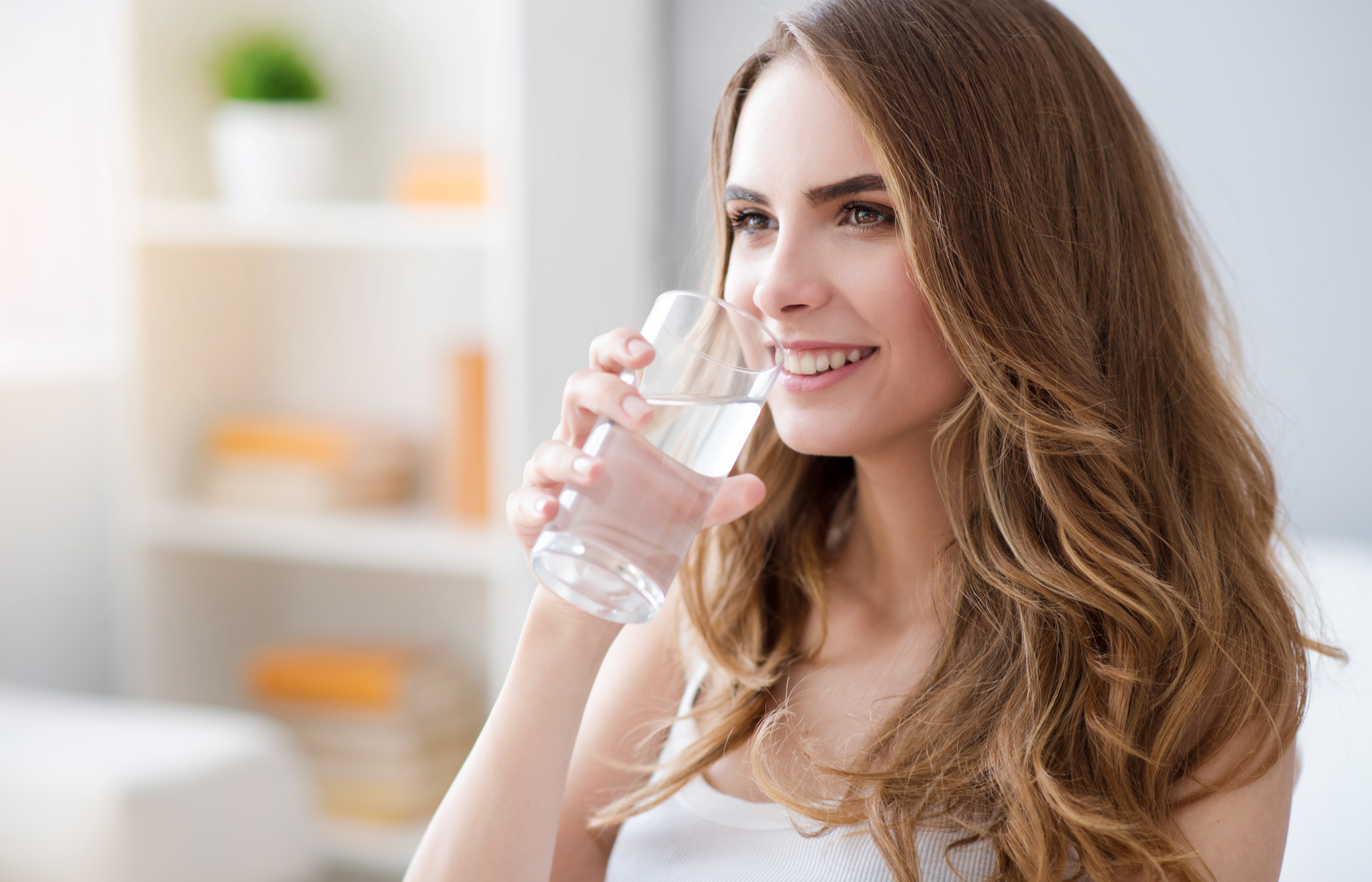 My dose of positivity. Cheerful delighted beautiful woman holding glass and drinking water while smiling